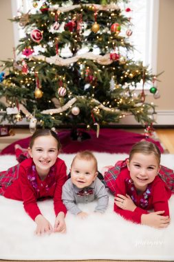 children next to christmas holiday tree