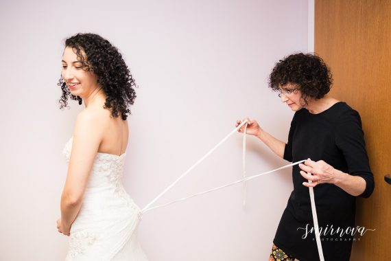 mom tying wedding dress